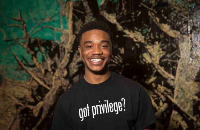 "Headshot of a young man with short black hair, smiling, wearing a black shirt that reads ""Got Privilege?"", in front of a mural of a tree."