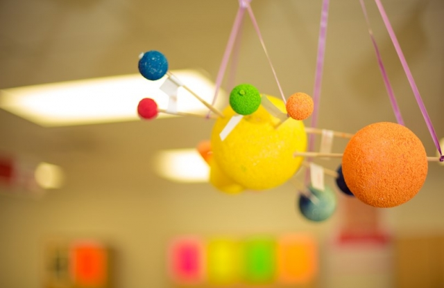 A colorful, hand made mobile of the solar system, hanging from the ceiling of a classroom.