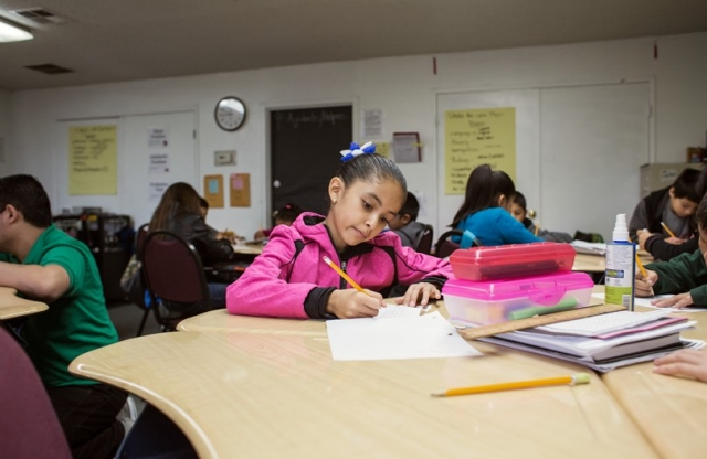 An elementary school girl with tied back hair in a pink sweater sitting at table with lot of school supplies writing an assignment in a classroom with many of her peers.