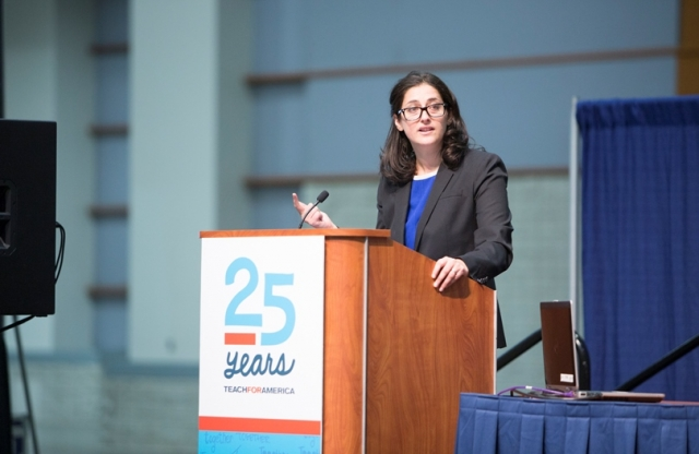 "A woman with brown hair and glasses, wearing a gray blazer stands behind a podium with a sign on it reading ""25 Yeaers"" and a blue curtain behind her, lifts her right hand as she speaks to the audience."
