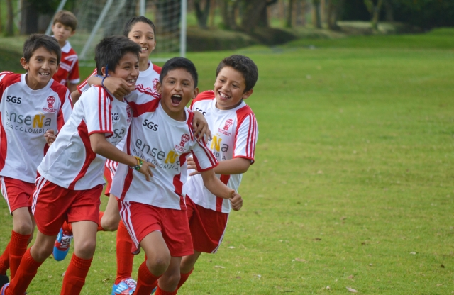 A group of six elementary school boys, all wearing red and white soccer uniforms, running and laughing, on a sunny soccer field.