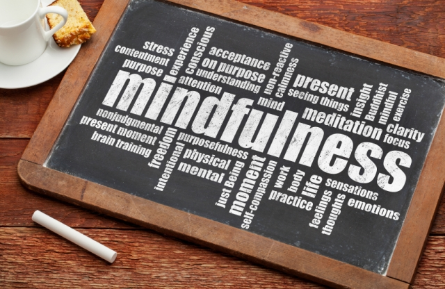 "A wood framed chalkboard with the word ""mindfulness"", as well as many others printend onto it sits atop a wooden table next to an espresso cup and saucer with some cake and a piece of chalk."