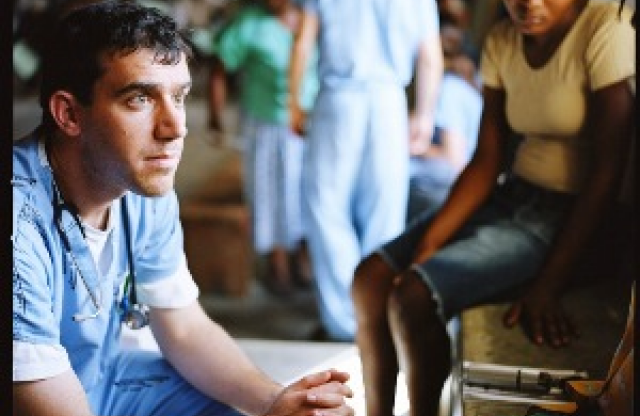 A younger man with short black hair wearing blue medical scrubs and a stethoscope sitting with his hands held together in front of him looking at the person in front of him, in a hallway with many people walking around.