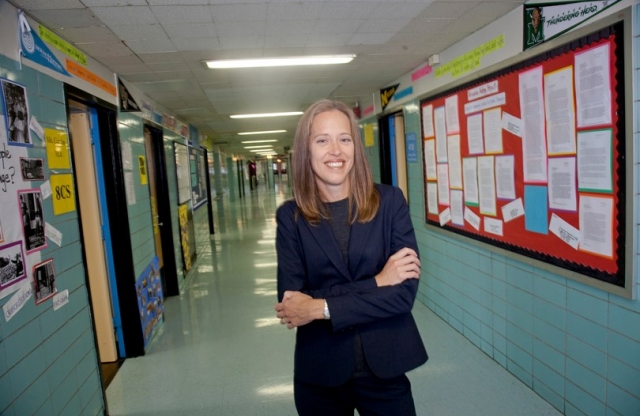 A middle aged woman with blonde hair, wearing a dark blue suit stands, smiling, in an empty school hallway with blue tile walls covered in bulliten boards and posters.