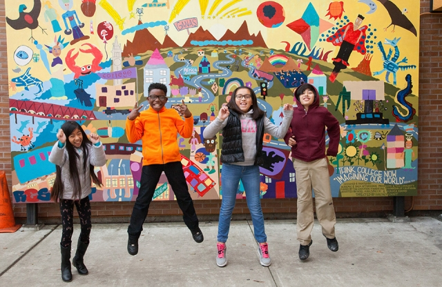 Four middle-school children jumping in the air in front of a colorful wall mural outside their school.