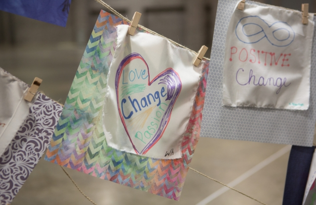 "Colorful banners with written statements in crayon stating 'Love, change, passion"" and 'Positive change' suspended from twine with clothes pins."