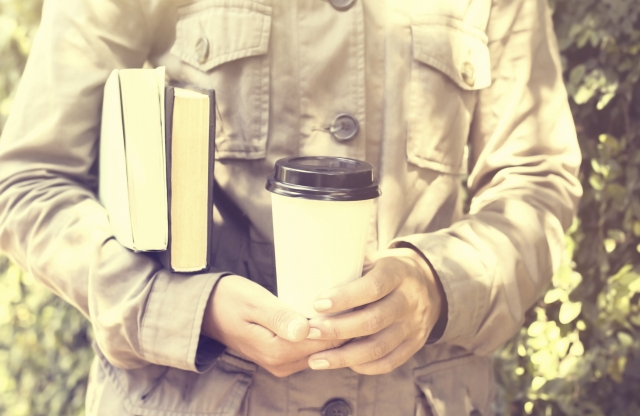 Close up of torso wearing a beige khaki jacket, holding a reusable coffee cup in front of them and two books under the right arm.