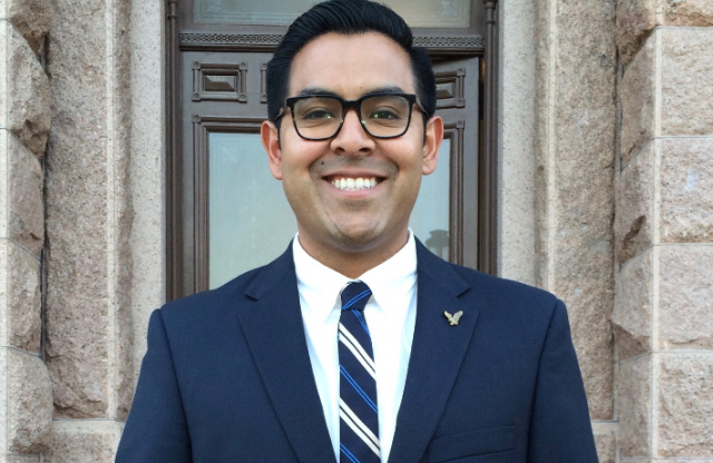 Head shot shot of a young man with slicked back black hair and black framed glasses wearing a blue blazer, white button down shirt and a blue and white striped tie, smiling in a stone doorway.