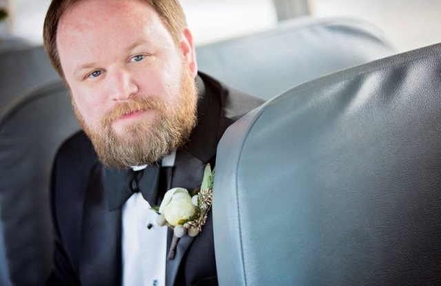 A young man with short ginger hair and a bushy ginger beard wearing a tuxedo with bow-tie and a white flower in his lapel smiling on a school bus seat.
