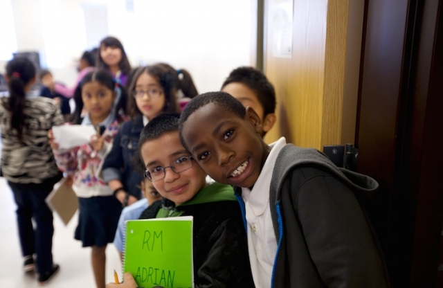 A class of elementary students stand in a line extending from the foreground into the background, smiling while they look towards the camera.