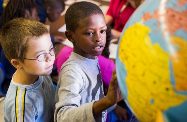 Two young boys looking at a globe in the classroom