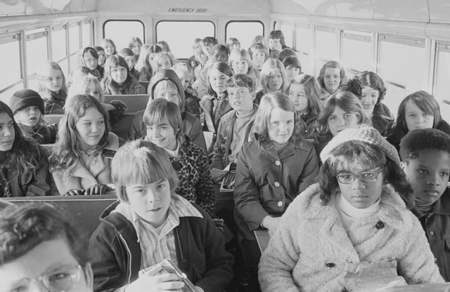 Black and white students ride a bus to an integrated school.
