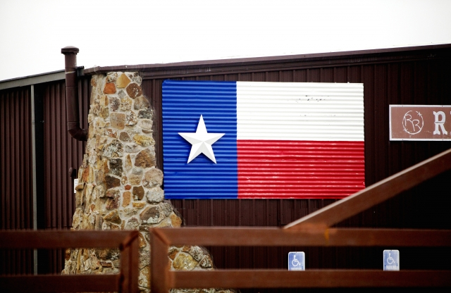 The flag of Texas made with corrugated metal, hanging on the side of a brown, metal siding building with stone bricked corners, behind a low metal gate.
