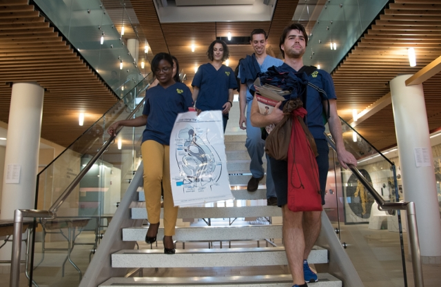 Four medical students walk down stairs