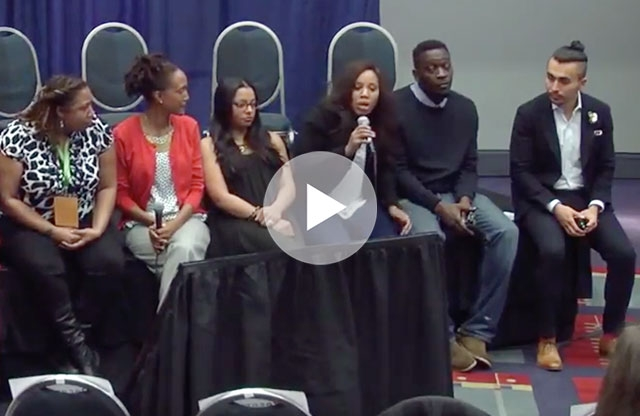 Screenshot from a video showing a group of four young women and two young men sit on the edge of a stage, with chairs and a blue backdrop, and hold microphones in their hands while the woman in the center speaks to the audience.