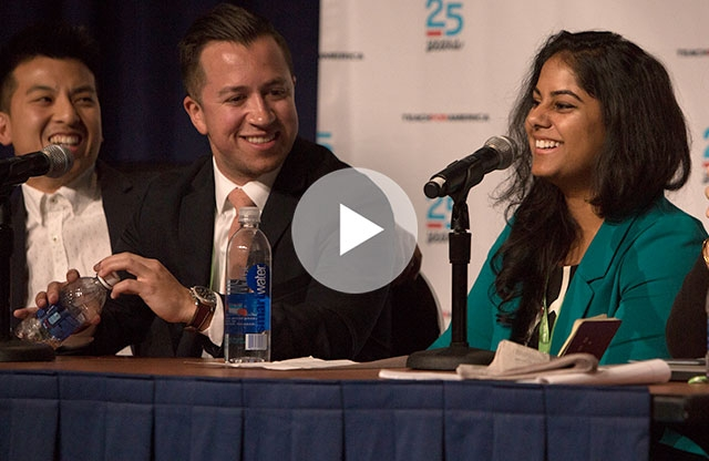 Screenshot from a video showing a young woman with long brown hair, smiling, with two young men looking at her and smiling while they are all sitting at a table with microphones.