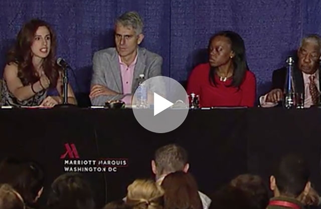 Screenshot from a video showing a panel of two men and two women sitting behind a table with a black skirt, backed by a blue curtain, in front of an audience.