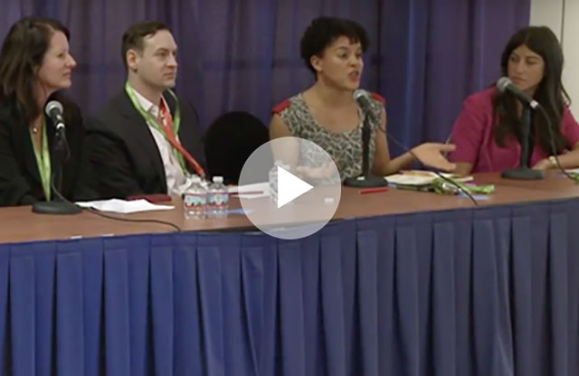 Screenshot from a video showing a woman seated behind a table with a blue skirt, speaking into a microphone while a man and two other women sit with her with their own microphones, listening, in front of a blue curtain.