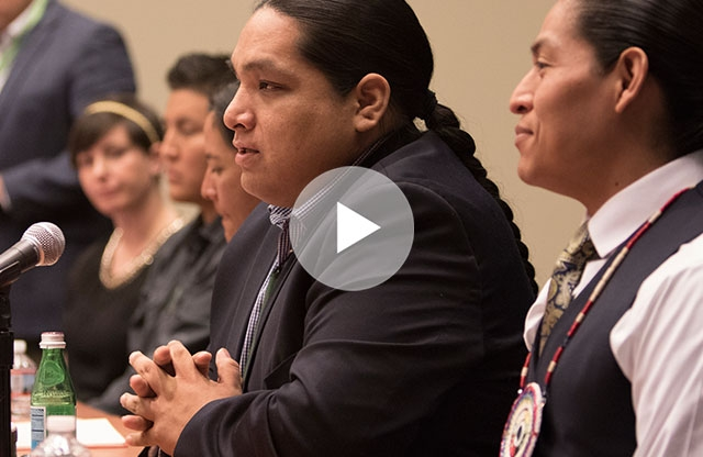 Screenshot from a video showing a man with braided black hair wearing a black blazer speaking into a microphone at a table while people around him smile and listen.