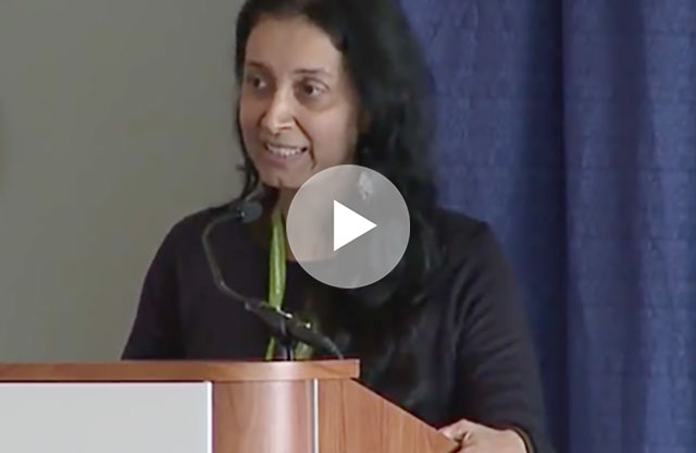 Screenshot from a video showing a middle aged woman with long black hair wearing a black shirt behind a podium speaking into a microphone in front of a gray wall and blue curtain.