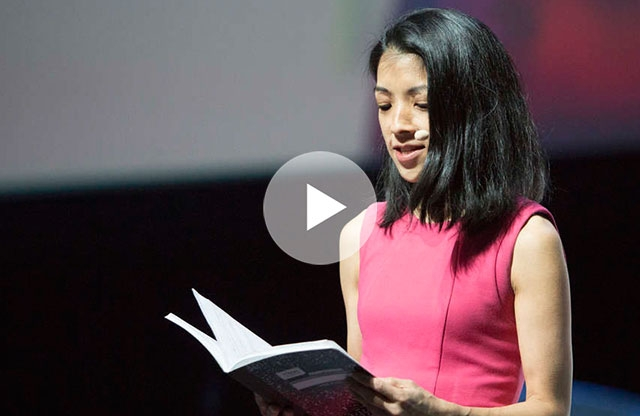 Screen capture from a video showing a young woman with shoulder length black hair wearing a pink sleeveless shirt speaks into a wireless microphone while reading from a book on stage.