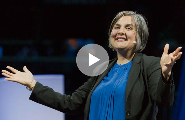 Screen capture from a video showing a middle-aged woman with shoulder length silver hair wearing a blue shirt and black sweater and a wireless microphone, smiling, and holding her open hands out to each side, standing on a stage.