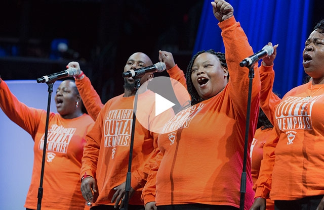Screenshot of a video showing four people, three women and one man, standing onstage in front of microphones, wearing orange sweatshirts and singing with their arms raised.