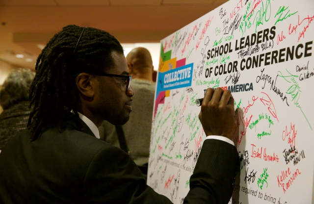 School leader signing name on poster for School Leaders of Color Conference