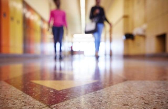 two blurred figures in school hallway