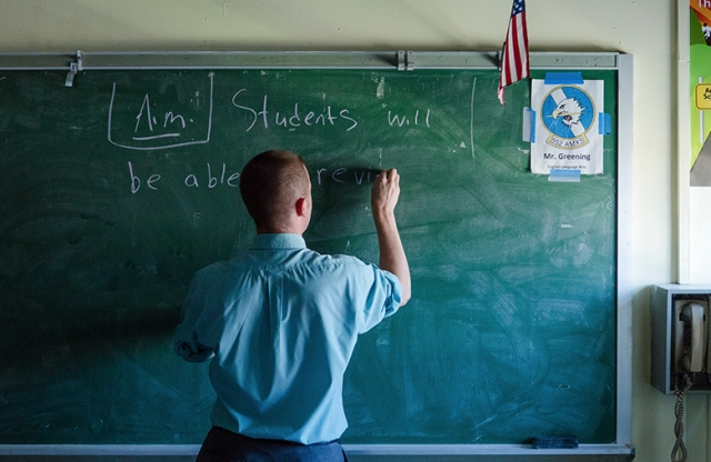 A Teach For America alumnus writing on a blackboard