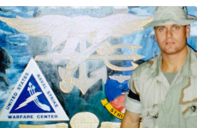 A young man in a short-sleeved military uniform with a gray hat standing in front of a wall covered in military insignia.