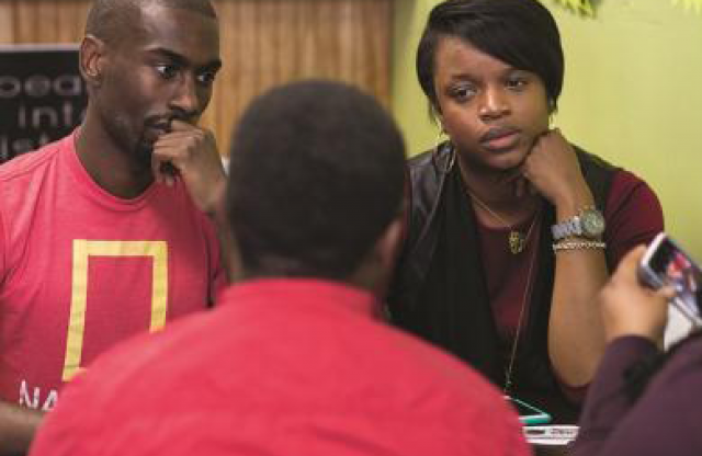 Two young men and two young women, all wearing red shirts, sitting at a table in a library, engaged in a lively discussion.