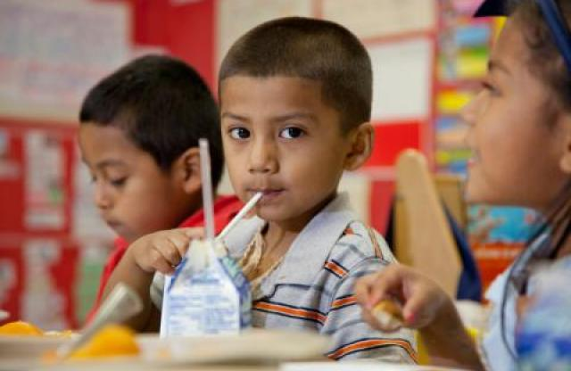 A very young boy with buzzed black hair drinks milk from a box with a straw in a classroom at lunch, while his classmates carry on an energetic conversation.
