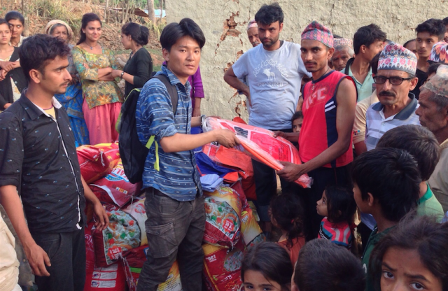 A middle-aged man with thick black hair and a blue shirt hands out care packages to a large group of Nepalese villagers.
