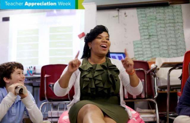 A middle-aged woman with straightened black hair wearing a green dress talking to middle-school students.