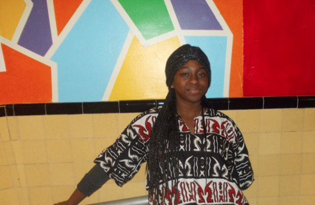 A female high-school student with long braided brown hair posing in front of a tiled wall with a colorful mural on it.