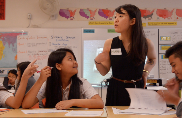 A young female teacher with long dark brown hair standing in her elementary-school classroom pointing at herself.