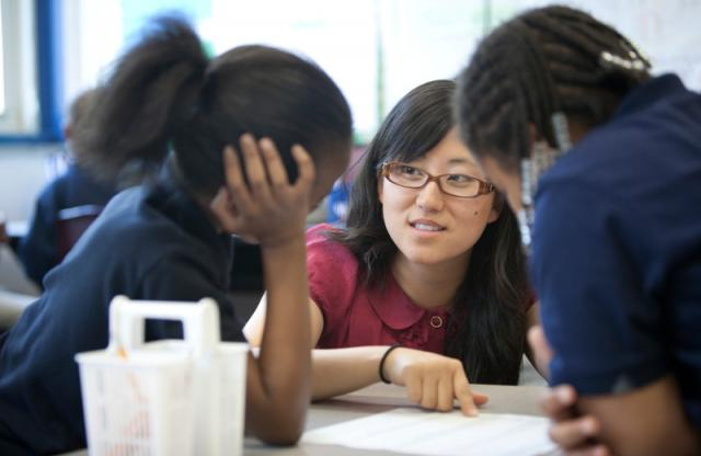A young female teacher with long straight black hair and red framed glasses explaining something to two students.