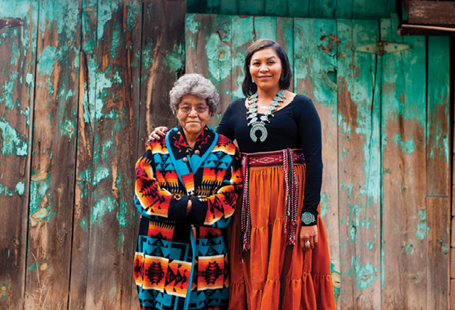 A young woman with her arm around an elderly woman, both smiling and wearing Native American dress, in front of a wooden wall with blue-green paint peeling from it.