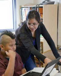 A young female teacher with long brown hair helps a middle-school boy with a mohawk with an assignment on his computer.