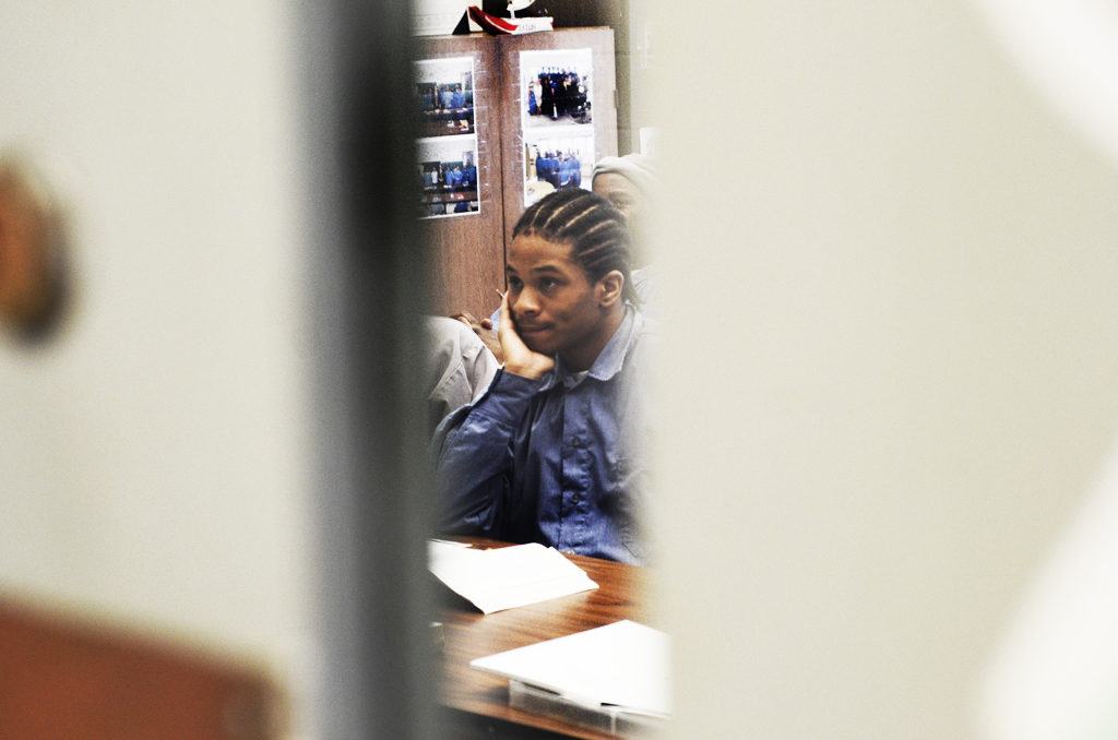 View from between doors of a young man with brown braided hair and a blue shirt attending a class, leaning his head on his hand.