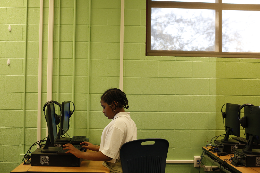 A middle-school aged girl with curly black hair in braids working at a computer, wearing a white polo shirt.