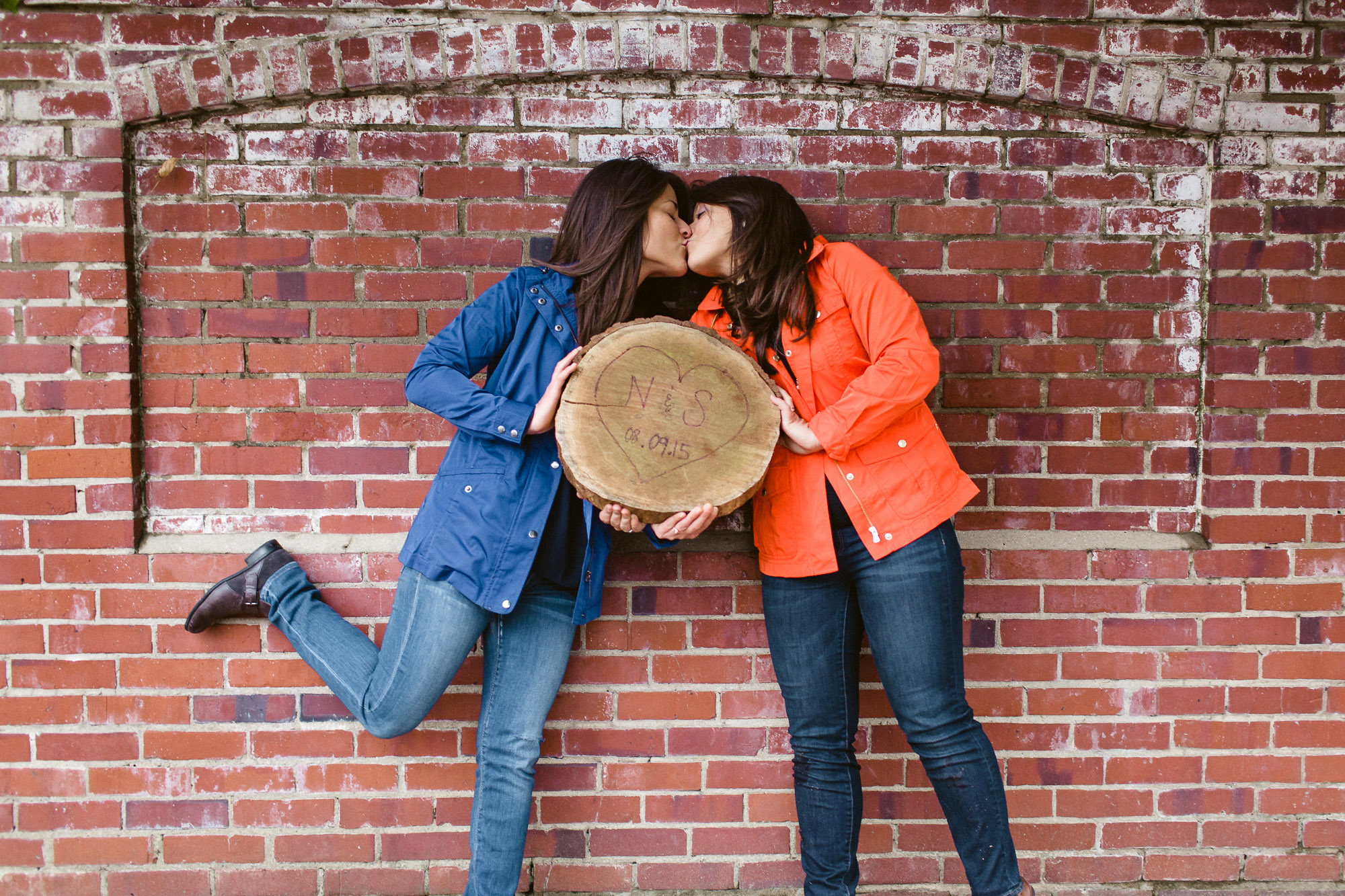 Two young women with long brown hair kissing in front of a brick wall, holding a piece of wood with a heart carved on it.