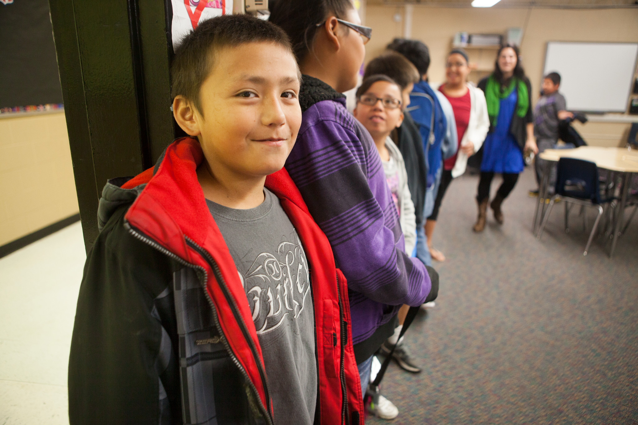 A line of middle-school students standing in a classroom, with one boy with short brown hair and a gray shirt smiling.