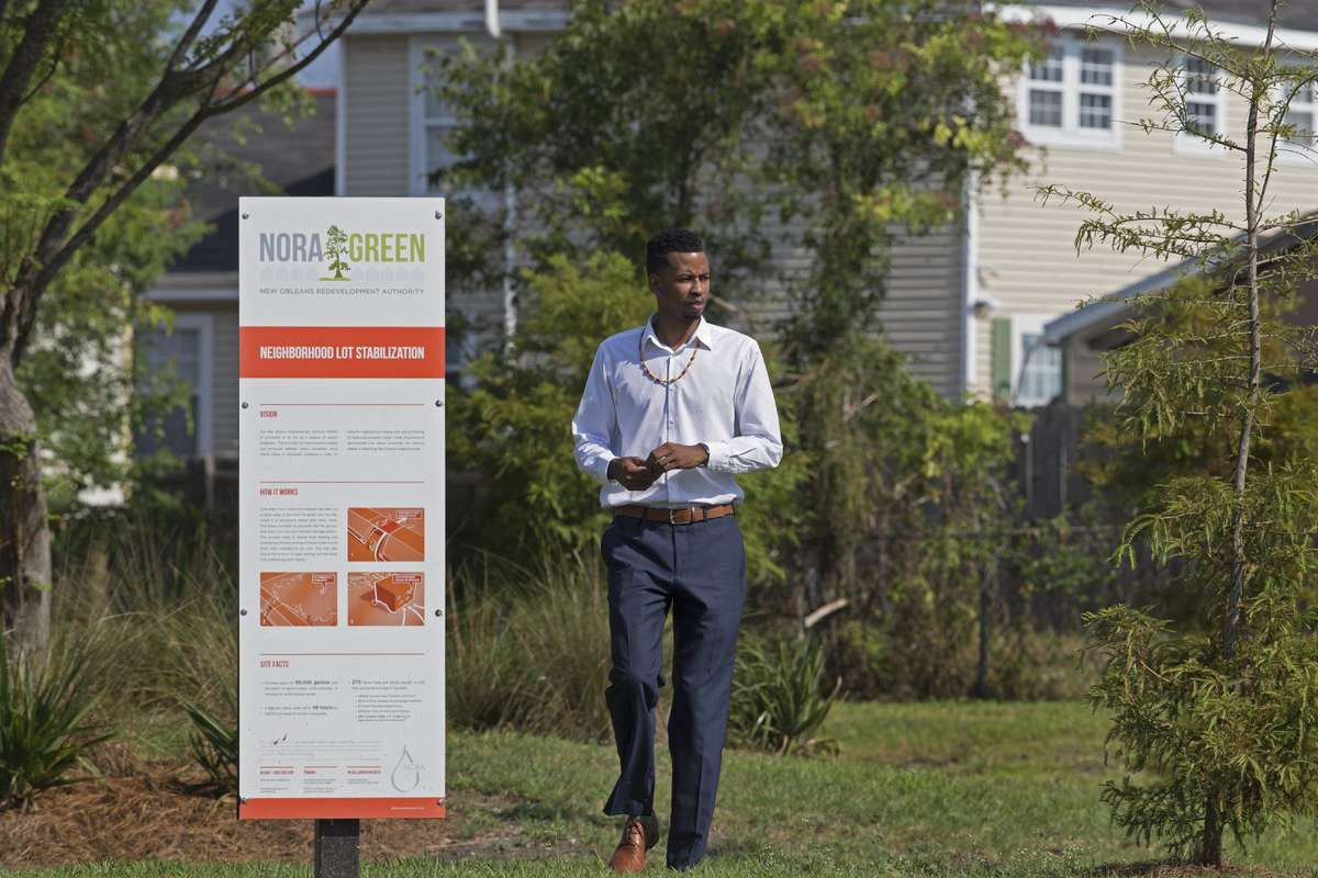 """A tall, slim young adult male in a collared shirt and slacks walks through grass; a beige house is in the background and a sign reading """"Nora Green"""" followed by a lot more nondescript, small text in the foreground."""