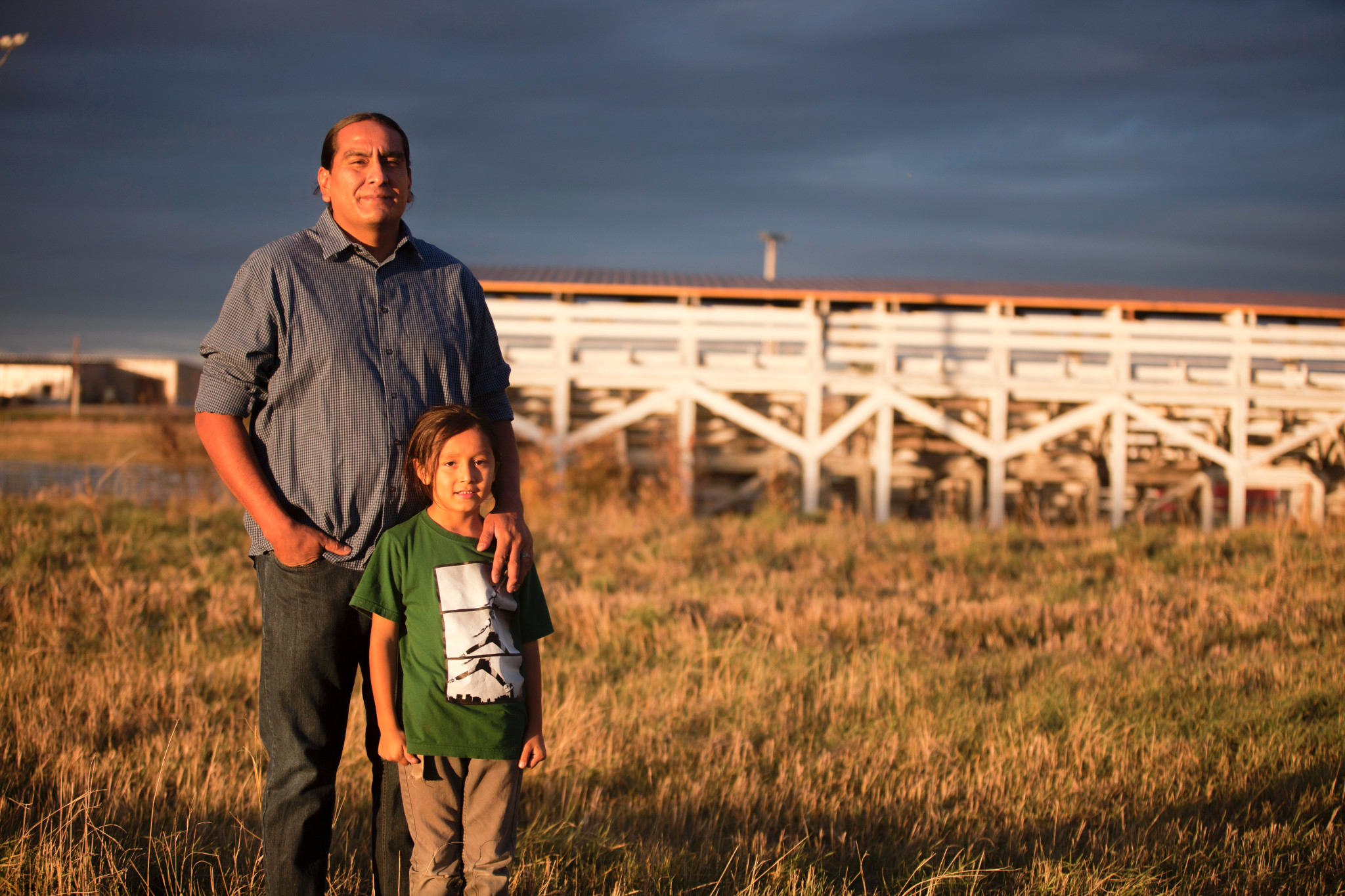 A middle-aged man and a young boy stand in a grassy field, both look off into the distance with a serious expression; a white wooden barn is in the background.