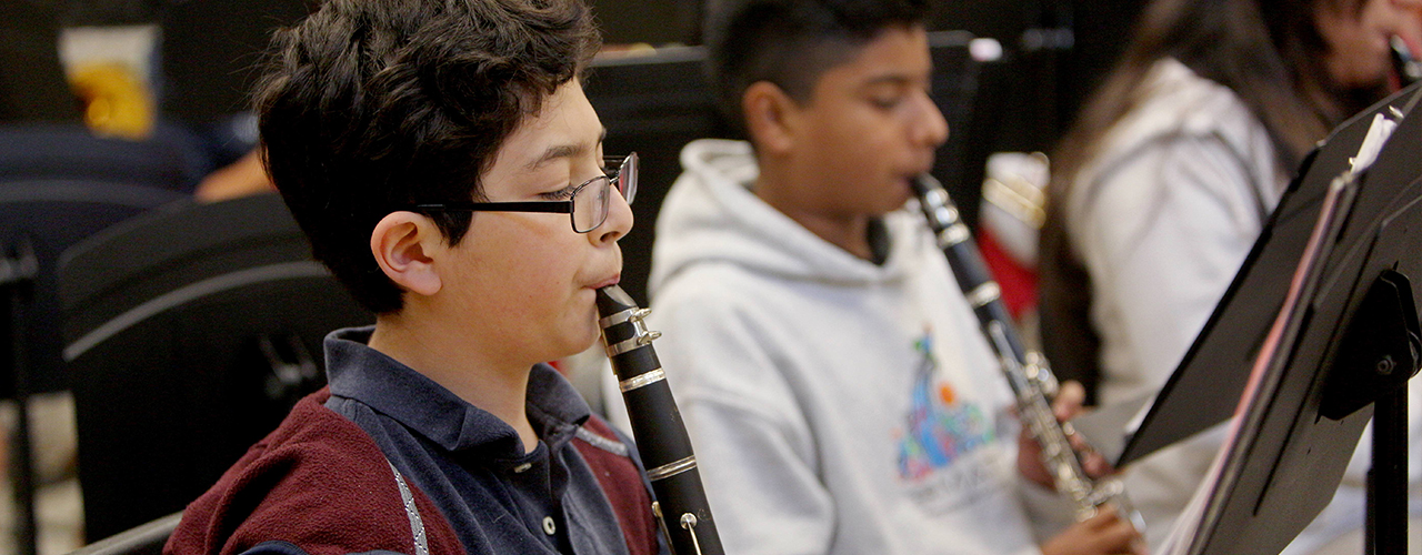 A middle-school aged boy with wavy brown hair and black frame glasses playing his clarinet intently in his music class.