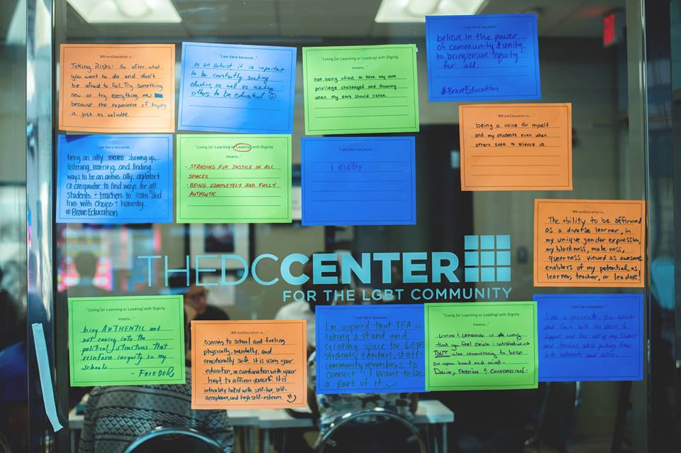 A glass room divider covered in sticky notes with inspirational messages.