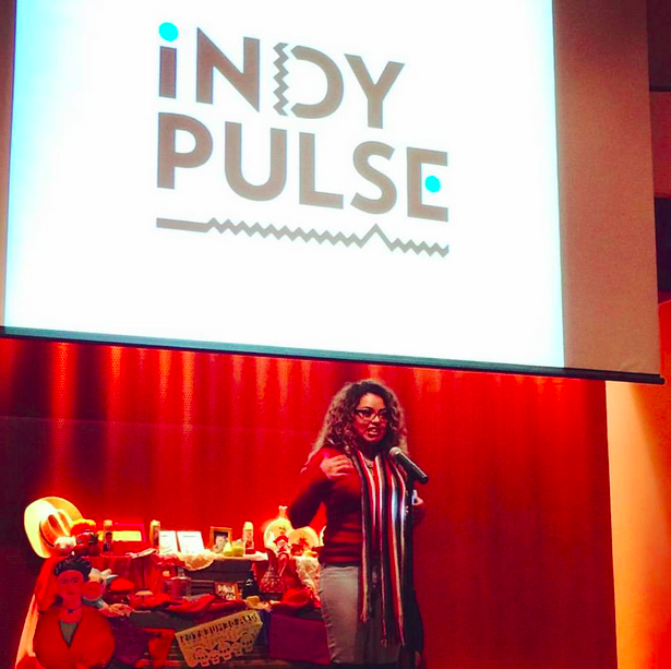 A woman singing into a microphone, in front of a projected logo for Indy Pulse