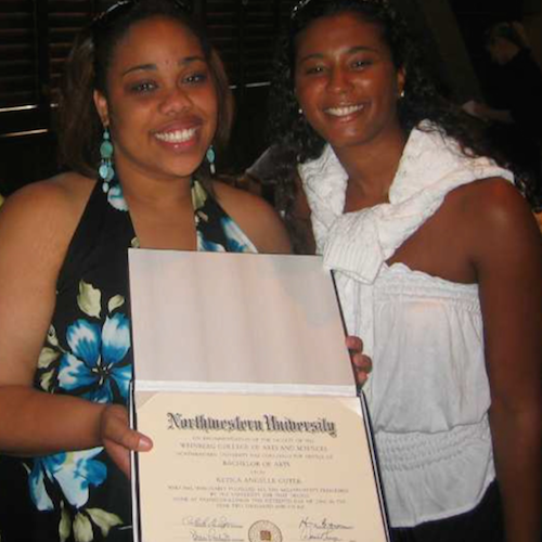 A young woman with brown hair holds a diploma, smiling beside her mother.
